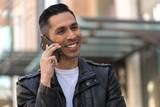 Hispanic man in city talking on cell phone - 199825664
