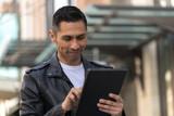 Hispanic man in city using tablet computer - 199825807