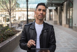 Hispanic man in city using tablet computer - 199825860