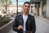Hispanic man in city using tablet computer - 199825861