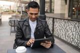 HIspanic man in city using tablet computer - 199826080