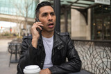 HIspanic man in city talking on cell phone - 199826405