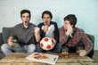 young group of happy and excited men watching a football game on the couch