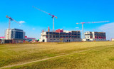 New construction site with cranes. Developer's project on green field. - 199833089