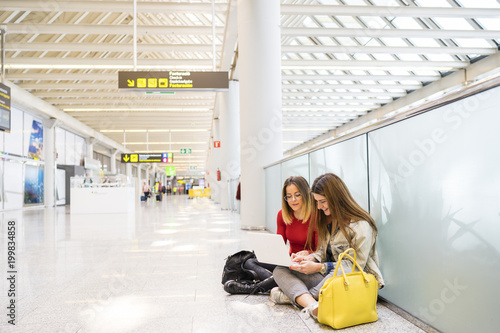 Girls at the airport searching the computer