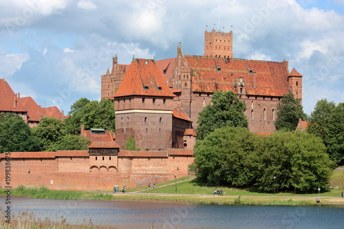 Widok na zamek krzyżacki w Malborku, Poslka, z drugiego brzegu rzeki Nogat, słon Poster
