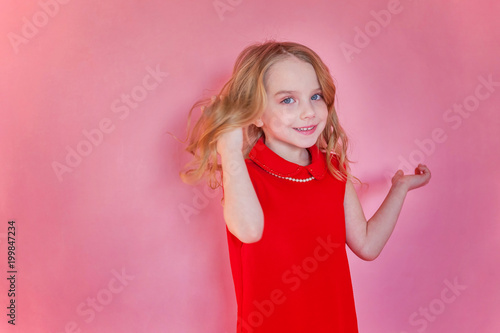 Little cute sweet smiling girl in red dress standing on pink colourful pastel trendy modern fashion pin-up background - 199847234