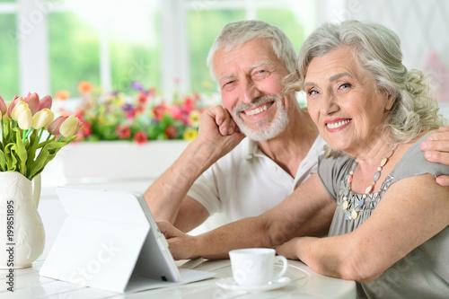 portrait of happy beautiful senior couple using tablet - 199851895