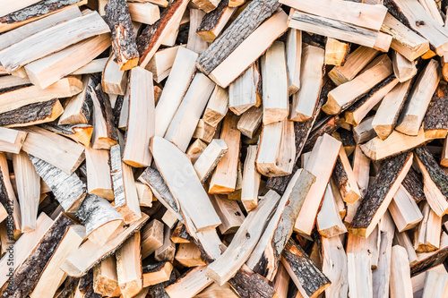 In de dag Brandhout textuur chaotically arranged in a pile of fresh chopped firewood, abstract background