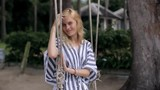 blonde woman on a swing in the tropics - 199890401