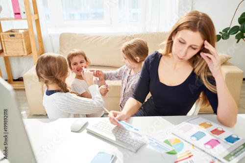 Busy manager sitting at desk and analyzing statistic data while her little daughters coloring their faces with red lipstick, interior of cozy living room on background