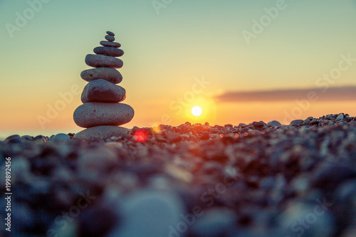 Foto op Plexiglas Zen Pyramid of stones on the beach at sunset, beautiful seascape, rest and seaside vacation concept