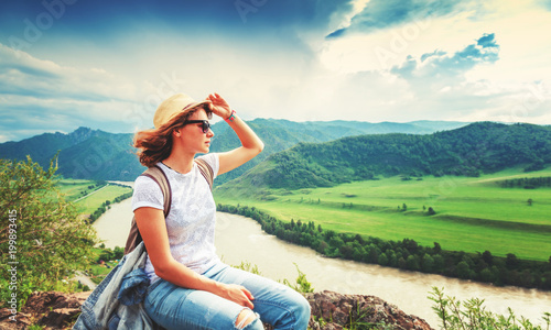 Beautiful young woman traveler travels through the mountains, sits on the rock and admires the valley at sunset