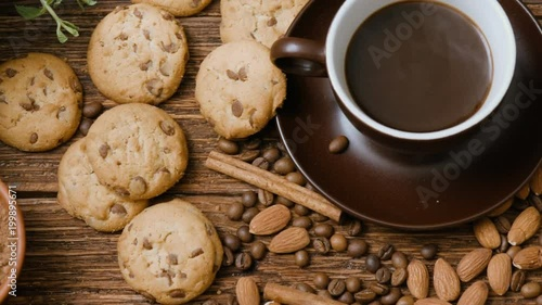 Coffee cup, beans, almond, chocolate and cookie on old kitchen table. Top view.