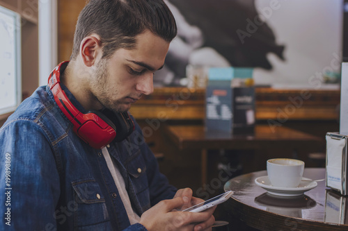 portrait of young with earphones and telephone in the cafeteria