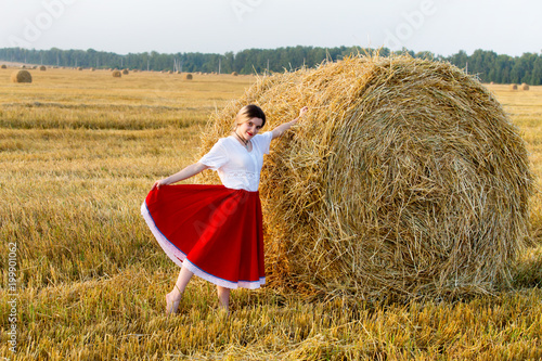 Lovely girl in a traditional costume walks on the field of cereals