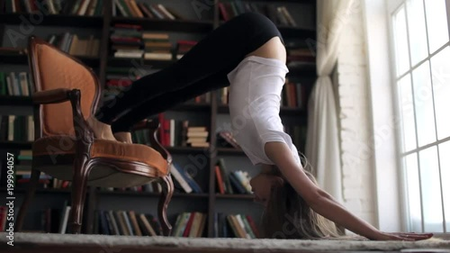 Obraz na płótnie slender woman practicing yoga at home on the chair