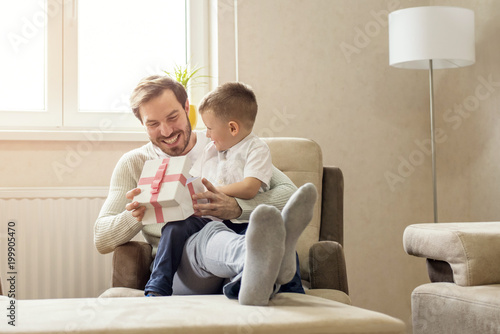 Little boy giving gift box to his father