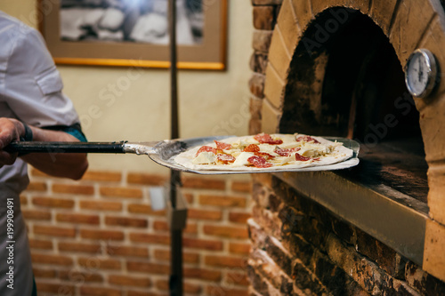 Foto op Plexiglas Pizzeria cook puts pizza with sausage, cheese, bacon and mushrooms in the oven