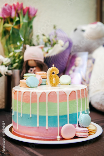 colored cake with macarons and festive candle for the child