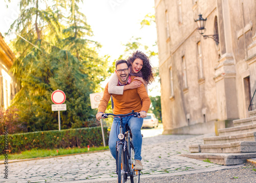 Foto Murales Happy young couple with a bicycle on sunny day in the city.