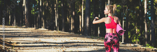 Foto op Aluminium School de yoga Young fit athletic woman in a forest wearing smart watch and holding yoga mat, walking away from the camera. Mind and body web banner.