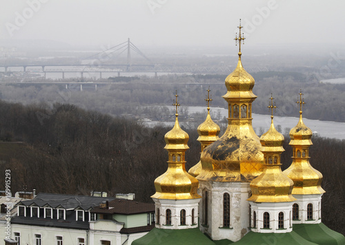 Foto op Plexiglas Kiev Golden domes of the Church of All Saints in Pechersk Lavra i Kiev, Ukraine. On the background the Pivnichnyi Bridge which crosses Dnieper River.