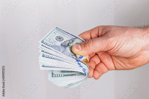 the man's hand holds a stack of dollars in dollars worth a hundred dollars on a light background