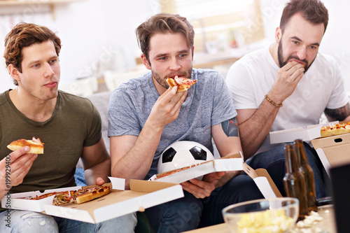 Foto Murales Happy male friends eating pizza and watching tv