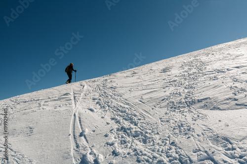 Alpinista ćwiczy skymo wspina się wzgórze z śniegiem