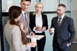 Group portrait of business team discussing work standing in hall of modern office building at coffee break holding cups