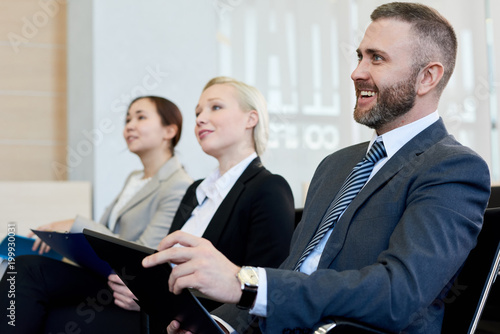 Group of smiling business people sitting in row in audience listening to training seminar, focus on handsome young businessman in front