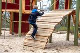 Happy boy climbing rope on the playground