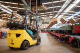 The forklift is in a large and light warehouse. Yellow color