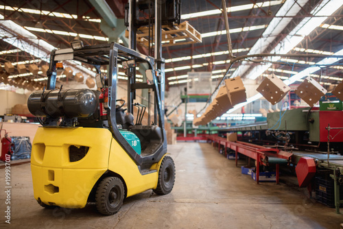 The forklift is in a large and light warehouse. Yellow color - 199937017