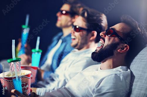 Grupa szczęśliwi przyjaciele siedzi w kinowym zegarka filmie i je popkorn