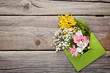 Bouquet of beautiful flowers with envelope on grey wooden table