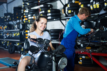 girl sitting on new motorbike in workshop.