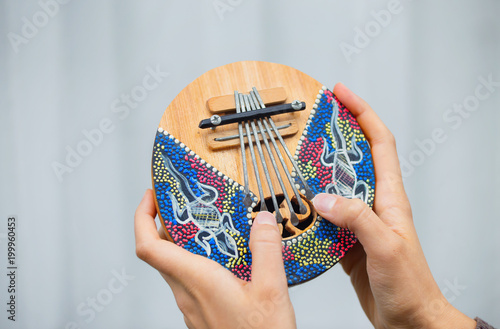 Womans hands with colorful musical instrument Kalimba. - 199960453
