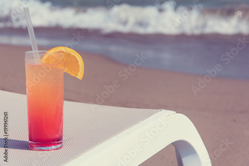 Foto Murales Glasses with colored cocktails on the beach with blue water in the background