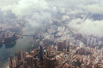 Aerial view through the clouds to a large metropolis city of Hong Kong.