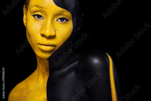 Black and yellow makeup. Cheerful young african woman with art fashion makeup.