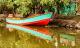 Small boat sits in water under trees with reflections in water