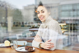 young smiling woman sits in cafe - 199973262