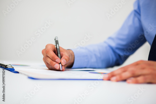 Closeup of a businessman writing documents - 199975824