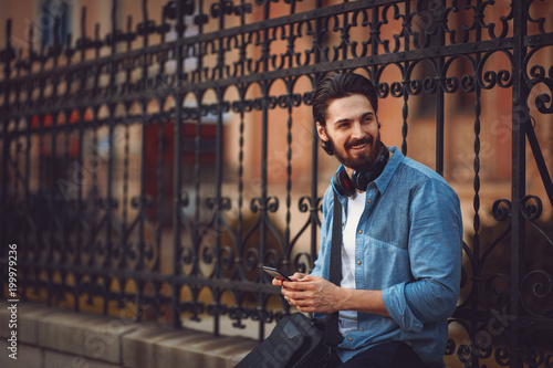 Foto Murales Young man texting on a smartphone