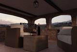 Steinmauer Terrasse mit Rattan Möbel im toskanischen Baustil vor wunderschönen Rebhängen und Sonnenuntergang. 3D Rendering - 199982297