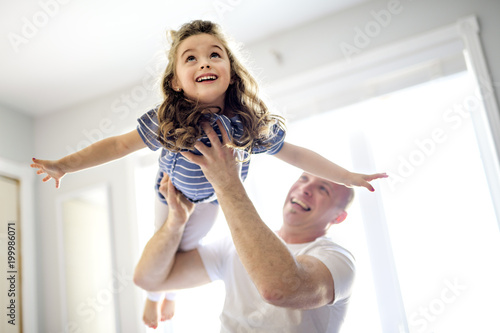 Happy father and daughter having fun together on a bed