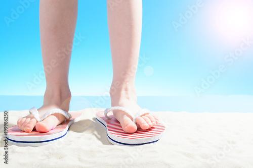 Foto Murales A little girl in flip flops stands on a sandy beach. body part
