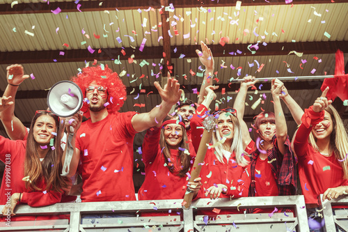 Foto Murales group of fans dressed in red color